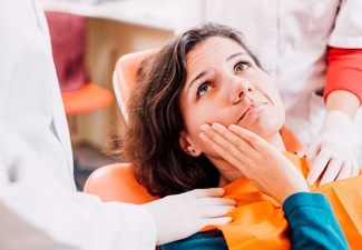 Woman in the dental chair touching her cheek