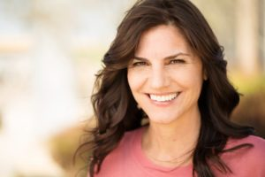 Woman smiling outside after visiting the dentist in Leawood