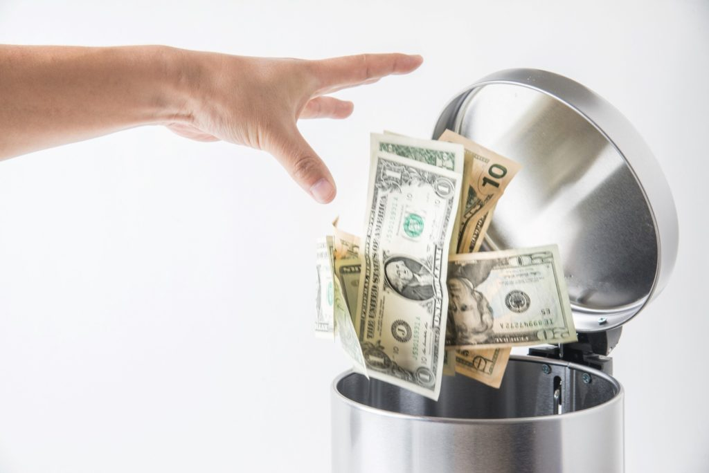Closeup of person throwing away money in the trash